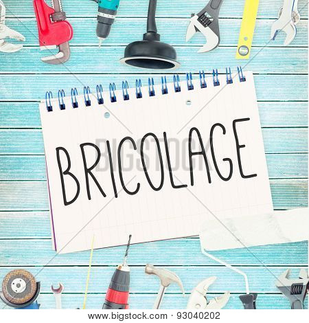 The word bricolage against tools and notepad on wooden background