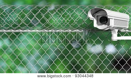 Security surveillance camera on chain-link fence on abstract nature background