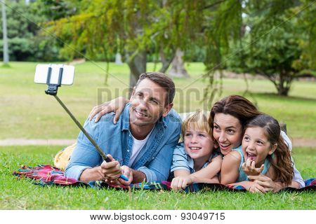Happy family in the park taking selfie on a sunny day