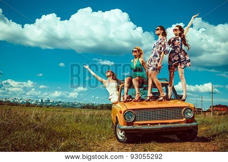 Four Beautiful Woman Are Dancing On The Old Car. Green Fields On The Background.