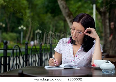 Girl With Notepad In Cafe