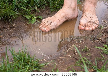 Feet Of Young Woman In Puddles After Rain, Closeup