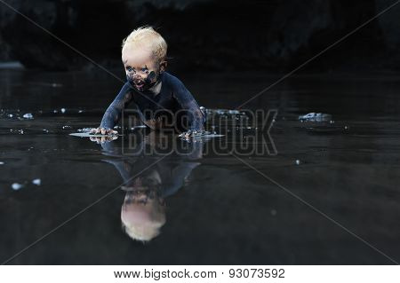 Dirty Child Crawling On Wet Black Sand Beach