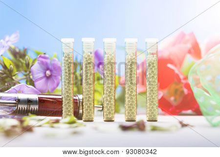 Small Glass Tubes With Homeopathy Globules, Syringe And Flowers