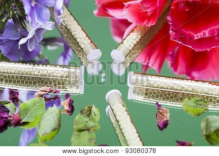 Small Glass Tubes With Homeopathy Globules And Flowers, Laying On A Mirror