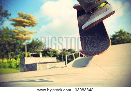 skateboarder legs doing a ollie trick at skatepark poster