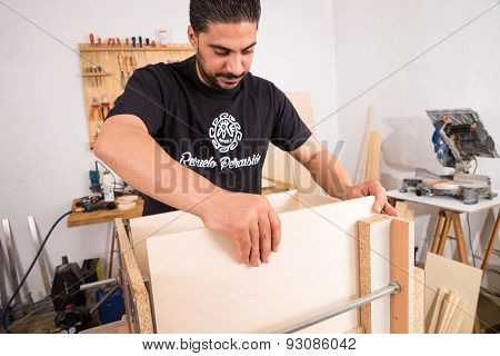 Artisan in his workshop assembling a cajon a flamenco percussion instrument poster
