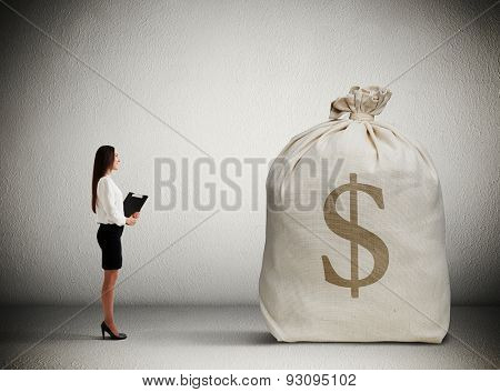 woman with folder standing in dark room and looking at big money bag