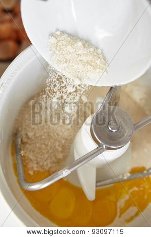 Adding ingredient to batter machine to make bread dough