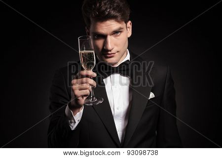 Handsome elegant man offering you a glass of champagne.