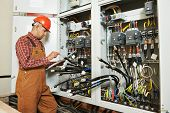 adult electrician builder engineer worker with electric scheme plan in front of fuse switch board poster