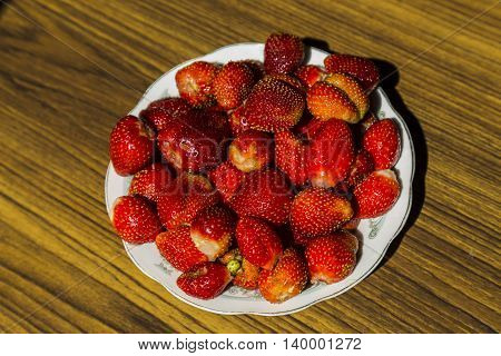 Plate with strawberries on wooden table top view