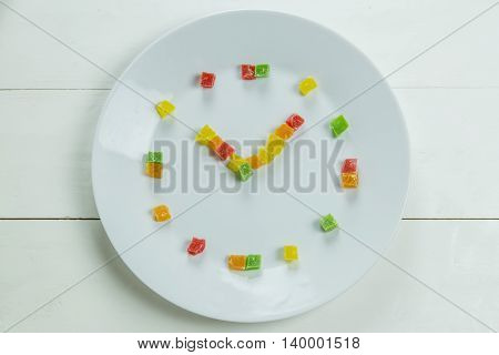 Fruit clock with candied fruits on wooden white background