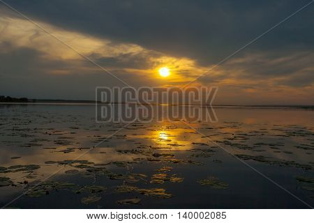 Golden sunset creeps over the clouds and sun reflected in the water surface of the lake