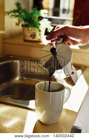 closeup of a young caucasian man serving coffee in a white mug from a moka pot in the kitchen