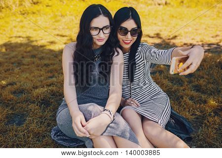 Two stylish girl walking in the park and make selfie