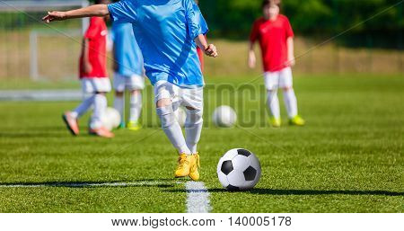 Children playing football soccer game on sports field.