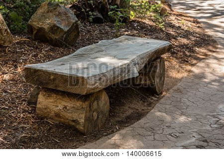 rough plank and logs wooden bench in shady park ecological materials