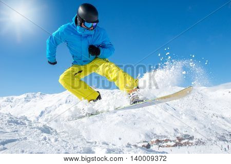 Active snowboarder jumping in mountains on a sunny day