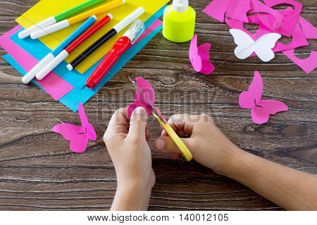 The Child Makes Decoration Paper Paper Butterfly In A Glass. Child Cuts The Paper Of The Product. Gl