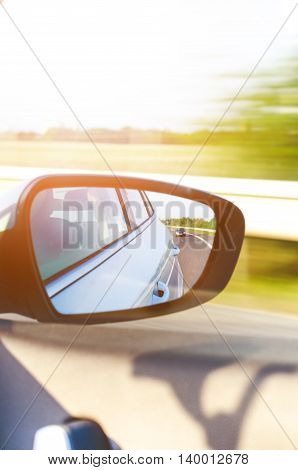 Concept of speed. Car driving on the road. Reflection in a car mirror.Rear view mirror reflection. Blurry background.