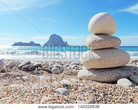 Balanced stones on the beach. View to the magic rock es Vedra in the background