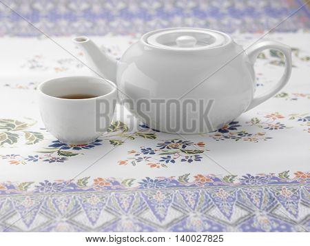 white tea pot and tea cup