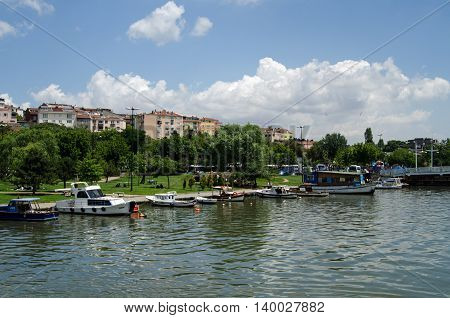 ISTANBUL TURKEY - JUNE 5 2016: Boats moored along the shore of the Golden Horn with families enjoying a sunny Sunday afternoon in Haskoy Park in the Beyogly district of Istanbul Turkey.