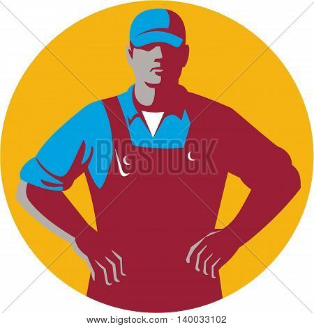 Illustration of an organic farmer wearing hat and overalls with hands on hips akimbo facing front set inside circle on isolated background done in retro style.
