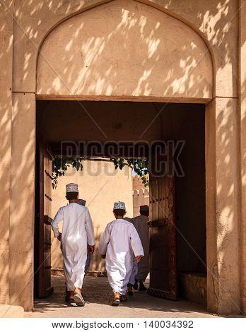 NIZWA, OMAN, MAY 27, 2016: Omani boys are walking through an alley in the old part of Nizwa village in Oman