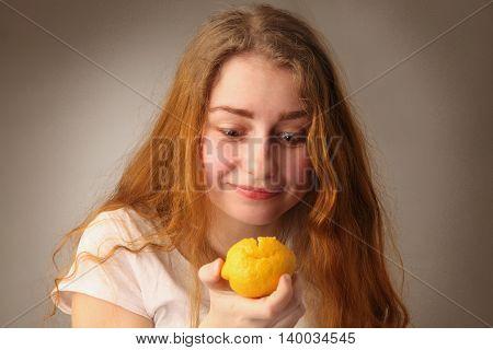 Close-up of a woman tasting sour lemon