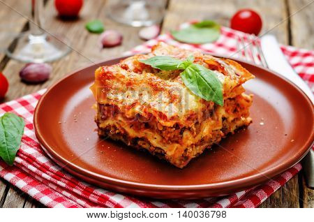 Meat lasagna on a dark wood background.