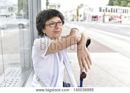 Senior woman with crutches waiting at bus stop