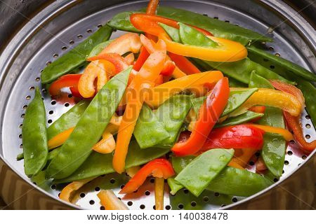 Bell pepper and snow pea stir-fry in stainless steel colander