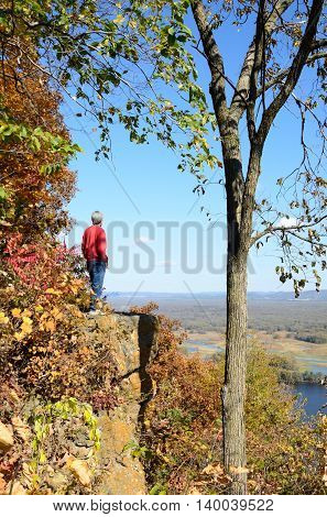 Man Standing on a Cliff Above the Mississippi River Valley in the Fall