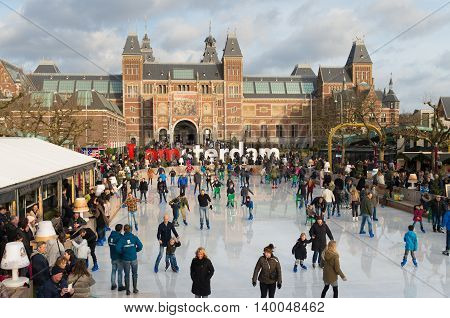 AMSTERDAM NETHERLANDS - DECEMBER 26 2015: People skating in front of the Amsterdam Rijksmuseum the largest and most inportant museum in the netherlands