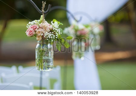 Rose bouquet hanging in mason jar at wedding