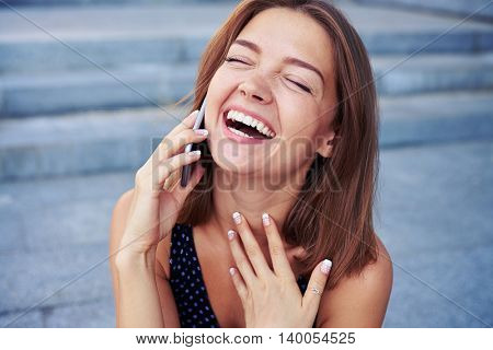 Attractive young female is speaking on the phone and laughing sincerely over grey street stairs background