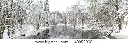 A cold and freezing river flows swiftly in a wintery Swedish scene.