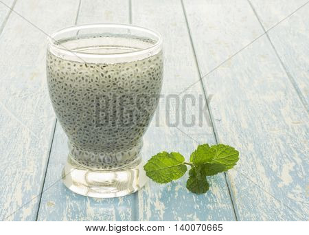 Sweet basil seed drink in glass of water on woodden background.