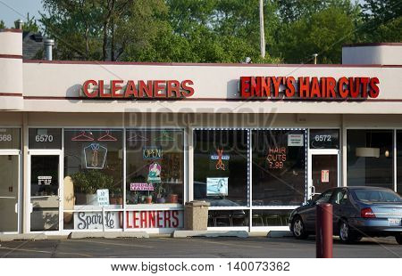 COUNTRYSIDE, ILLINOIS / UNITED STATES - MAY 21, 2016: One may have one's clothes cleaned at Sparkle Cleaners, and have one's hair cut at Enny's Haircuts, in a strip mall in Countryside, Illinois.