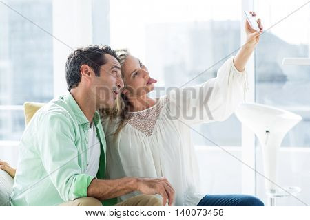 Happy couple making face while taking selfie against window at home