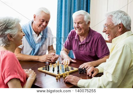 Seniors playing chess in a retirement home poster