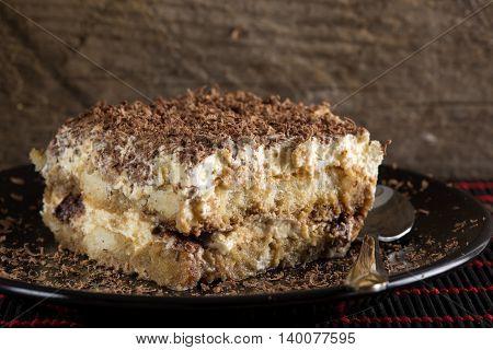 Tiramisu cake and spoon on dark plate with wooden background