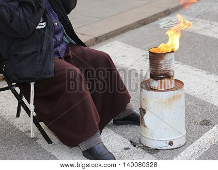 Poor Friar With Brown Frock Warms Up In Front Of The Bonfire