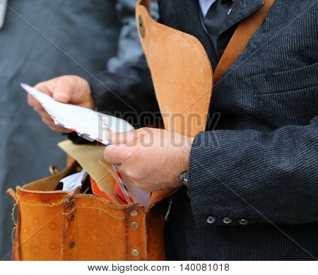 Postman With The Old Bag While Delivering Mail