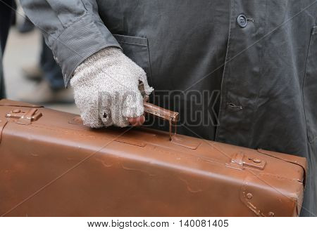 Migrant With Old Leather Suitcase And The Broken Glove