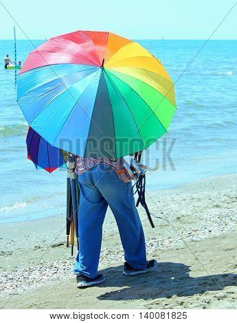 Poor Peddler Of Umbrellas On The Beach