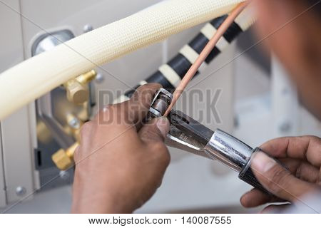 Worker Cutting Copper Pipe Of Air Conditioner