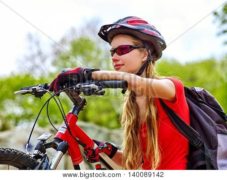Bikes bicyclist girl. Girl rides bicycle into mountains. Girl on bicycle in mountaineering . Girl carries her bike over rocks. Bicyclist looks forward faraway.